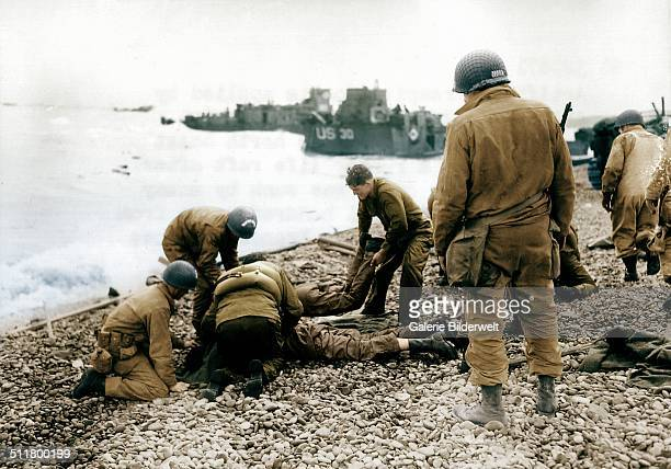 Operation Overlord On a pebble beach at Omaha Beach US soldiers deal with injuries 6th June 1944 All these men are from the 5th or 6th Engineer...
