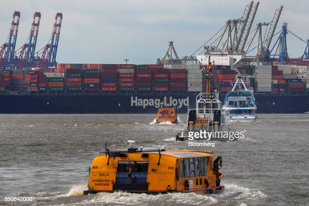 Operational port vessels sail as shipping containers sit on board a HapagLloyd AG container ship at the Port of Hamburg in Hamburg Germany on...