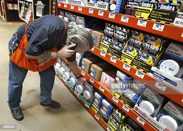 Operations manager Terry Phillips stocks Smoke and Carbon Monoxide alarms in a Home Depot store February 19 2004 in Mount Prospect Illinois United...