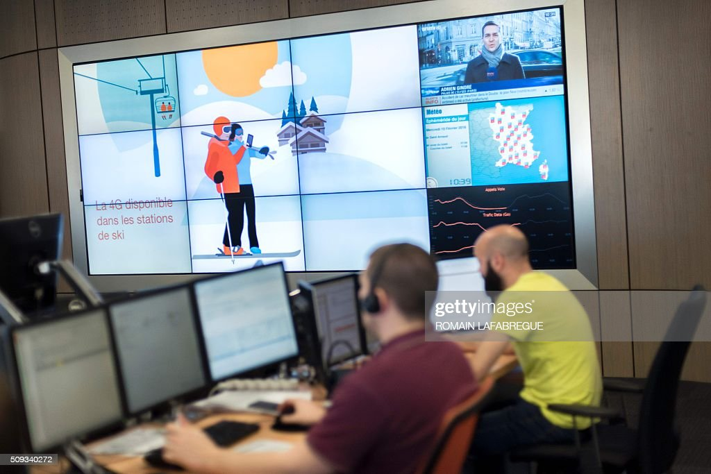 Operators work in front of a screen displaying a promotional graphic advertising the availability of the 4G network at ski resorts at Orange's mobile phone supervision center in Lyon on February 10, 2016. / AFP / ROMAIN LAFABREGUE