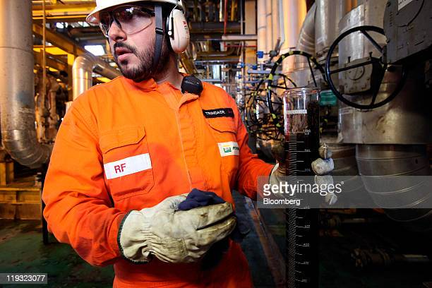 Opertations technician Thiago Trindade Camara tests an oil sample for water content on Petroleo Brasileiro SA's P51 oil platform in the Marlim Sul...