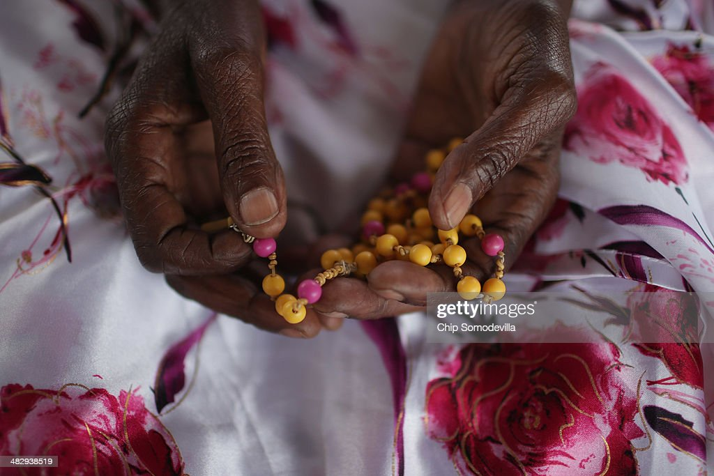 Ophelia Nyiramagumeri holds a rosary given to her by her nephew who was killed in the 1994 genocide while gathering with thousands of others at the Kicukiro College of Technology to commemorate the 2,000 people who were abandoned by United Nations troops during the 1994 genocide April 5, 2014 in Kigali, Rwanda. On April 11, 1994, Belgian paratroopers who were part of the UNAMIR mission were ordered to leave the school grounds, abandoning the people to the national police and Interahamwe militia, who lead their victims to a garbage dump and slaughtered them. Rwanda is preparing to commemorate the 20th anniversary of the country's 1994 genocide, when more than 800,000 ethnic Tutsi and moderate Hutus were slaughtered over a 100 day period.