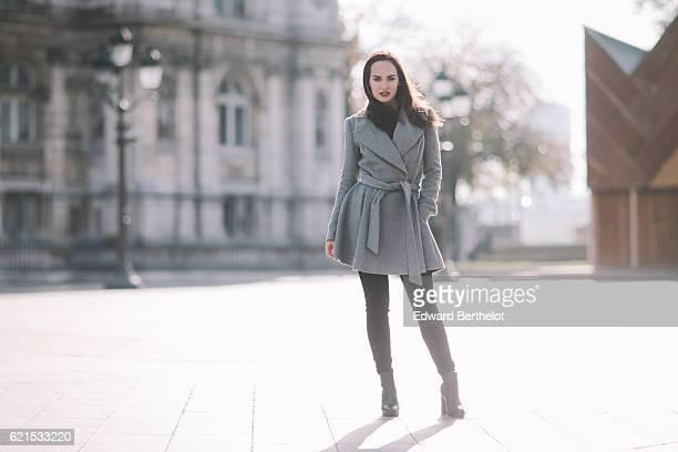 Ophelie Duvillard wears Zara black denim jeans a Derhy black top an Asos long gray coat Primary black boots and is using Tarte lipstick at Hotel de...