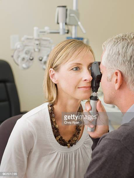 Ophthalmologist giving patient eye exam
