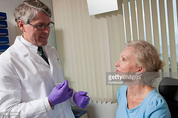 Ophthalmologist talking to a patient before giving injectable treatment