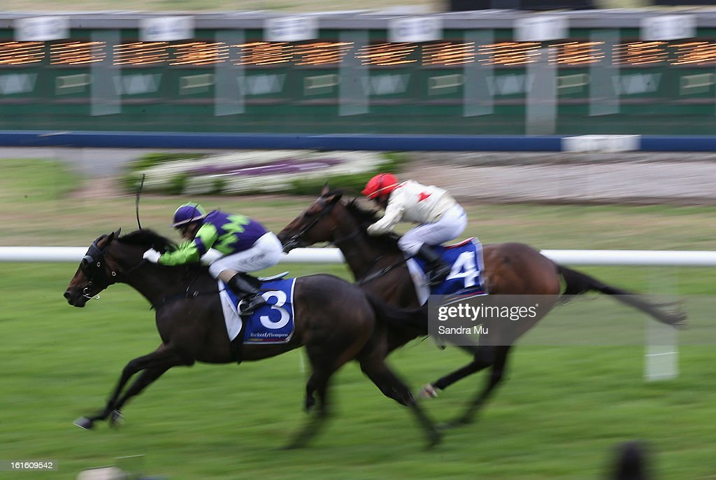 Opie Bosson riding Dubai Shuffle (L) wins race one ahead of Cameron Lammas riding Ribbony Rose during the Auckland Twilight races at Ellerslie Racecoourse on February 13, 2013 in Auckland, New Zealand.