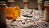 Prescription medication is strewn out upon US currency.