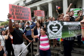 Opponents of samesex marriage stand behind a railing near supporters of the LGBTQ couples who are inside the courthouse asking the state of Florida...