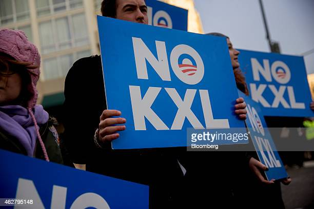 Opponents of the Keystone XL pipeline hold signs during a demonstration across the street where US President Barack Obama will attend an event in...
