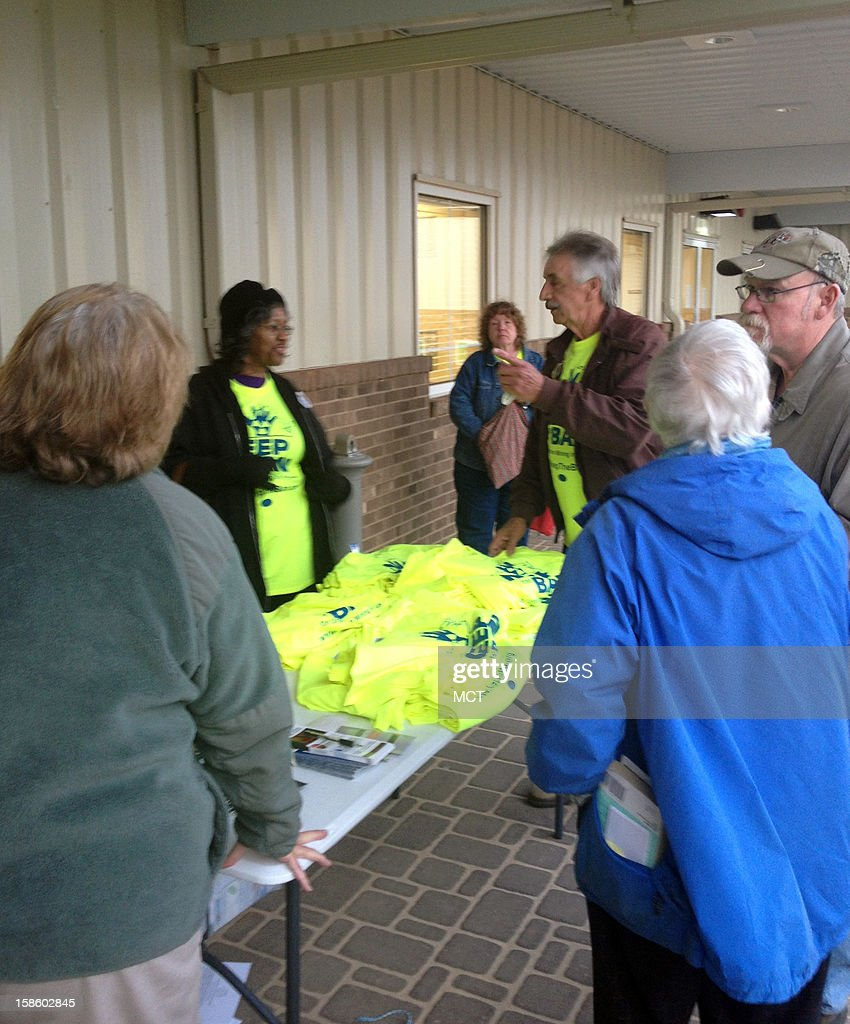 Opponents of uranium mining in Virginia gather outside a meeting near the mine site distributing neon yellow tshirts that say 'Keep the Ban'