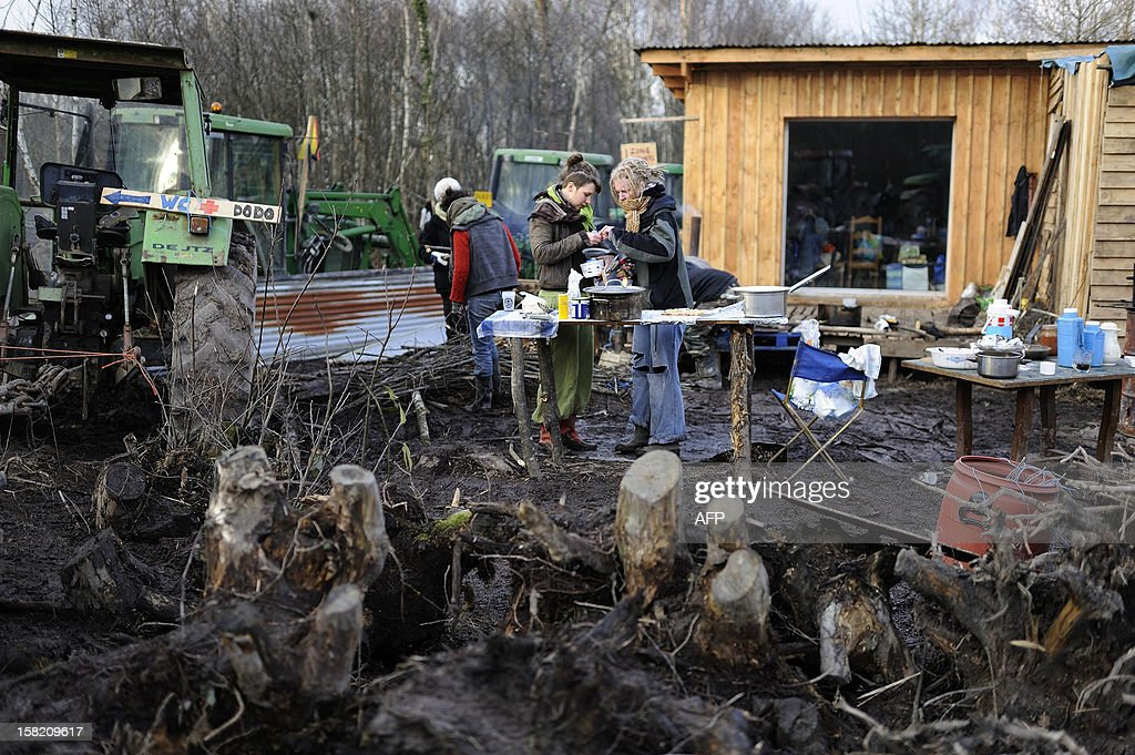 Opponents to an international airport project stand next to their shacks set within the ZAD ('Zone d'Aménagement Différé' a zone reserved for the later development of the project), on December 11, 2012 in Notre-Dame-des-Landes, western France. The vast stretch of woodland outside the tiny village of Notre-Dame-des-Landes is now Europe's biggest open air squat, according to the local police chief.