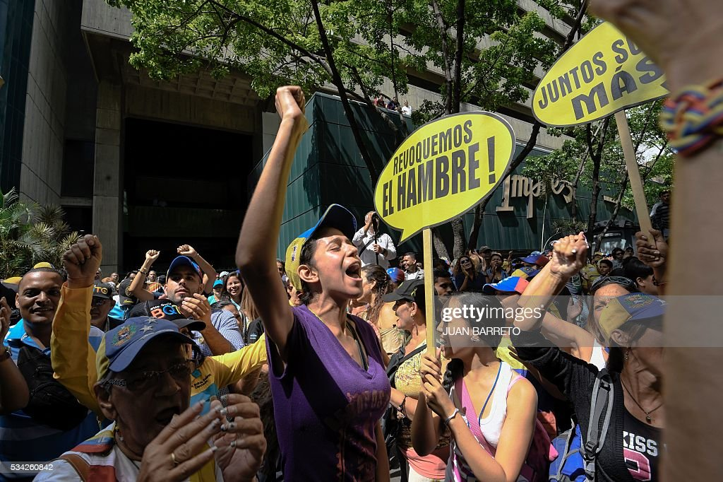 Opponents to the government of Venezuelan President Nicolas Maduro protest with signs reading 'Let's revoke hunger' outside the Supreme Tribunal of Justice (TSJ) in Caracas on May 25, 2016. Protesters seeking to drive Maduro from office launched fresh street rallies on Wednesday, a test of their strength in a tense political crisis. / AFP / JUAN