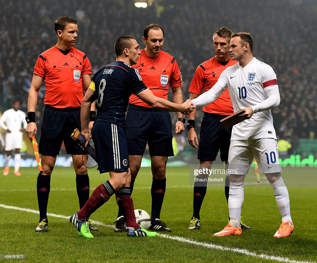 Opposing captains Scott Brown of Scotland and Wayne Rooney of England shake hands before kickoff during the International Friendly match between...