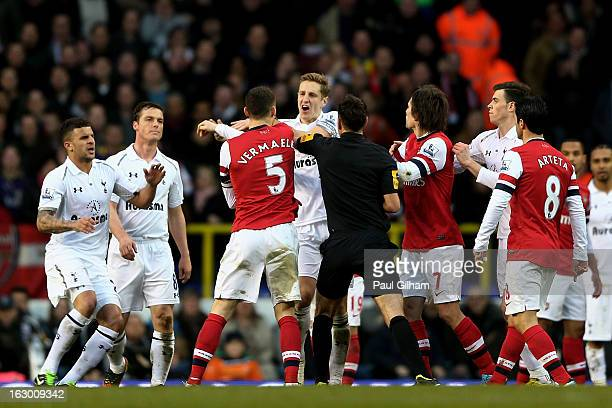 Opposing captains Thomas Vermaelen of Arsenal and Michael Dawson of Spurs clash during the Barclays Premier League match between Tottenham Hotspur...