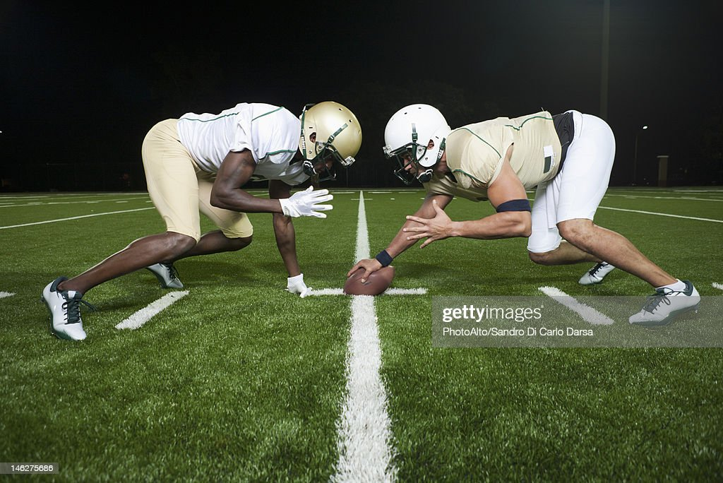 Opposing football players crouched at line of scrimmage