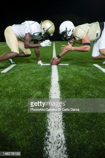 Opposing football players crouched at line of scrimmage : Stock Photo
