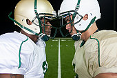 Opposing football players facing off