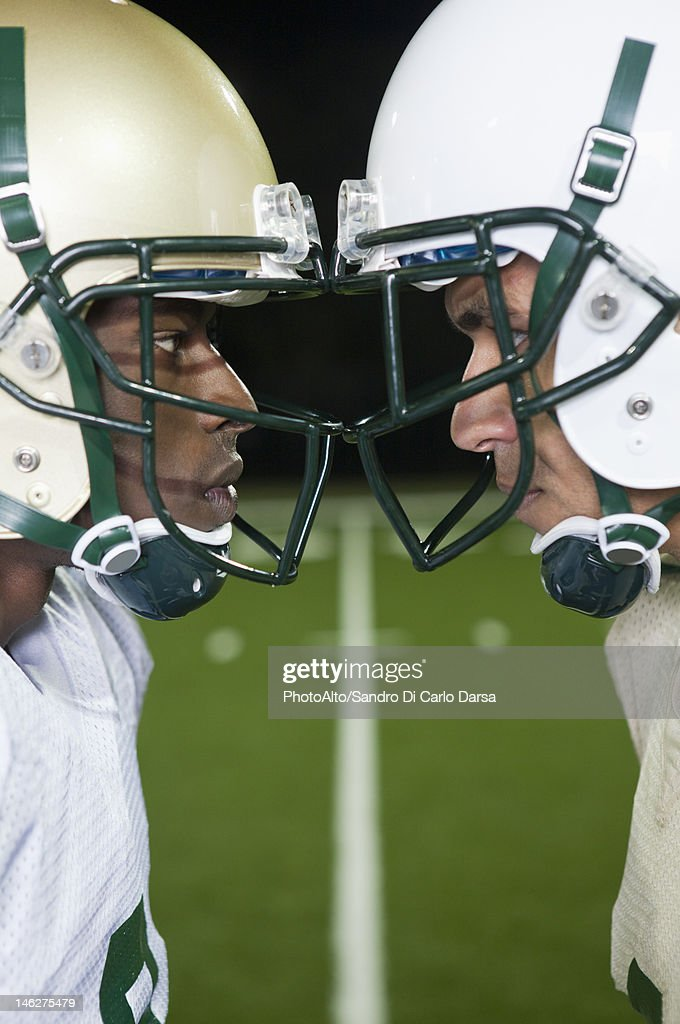 Opposing football players facing off : Stock Photo