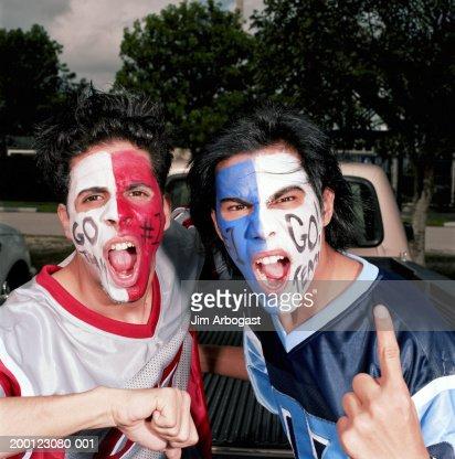 Opposing male sports fans wearing face paint, cheering, portrait