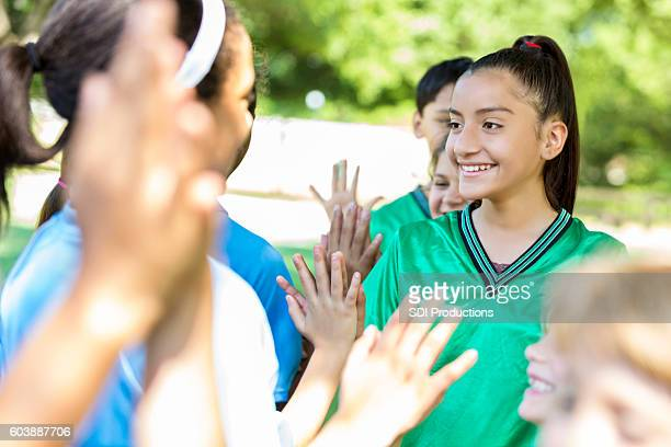 Opposing soccer teams line up for high fives after game