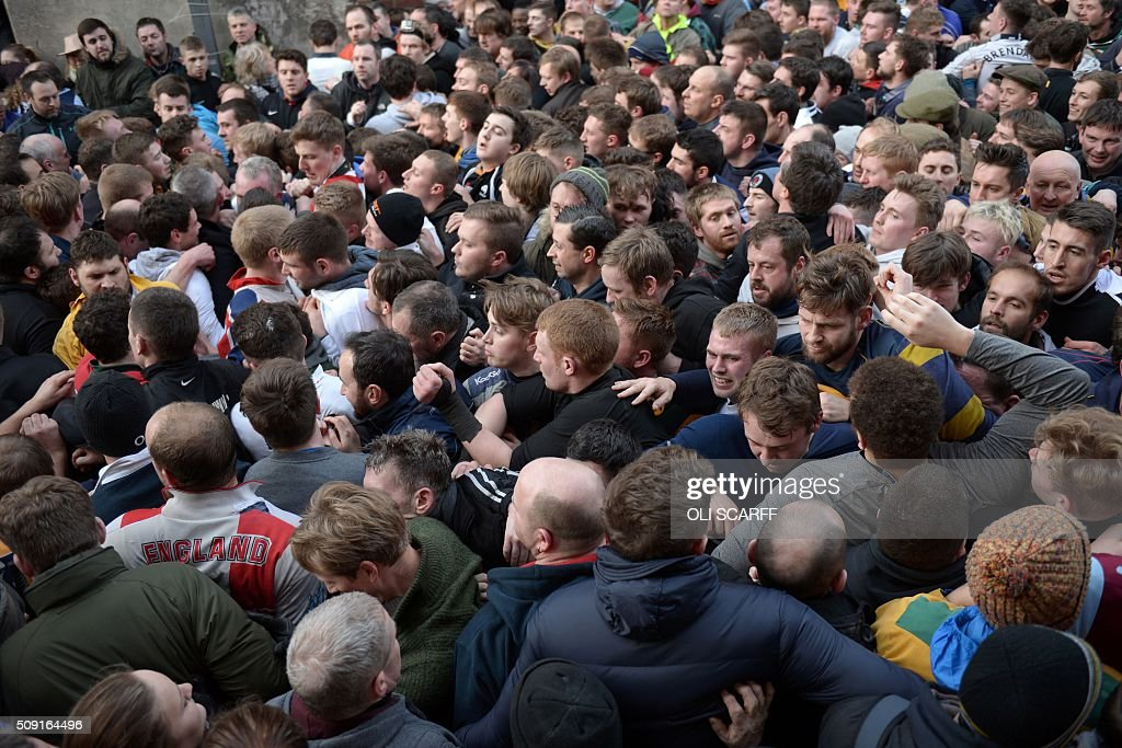 Opposing teams, the Up'ards and the Down'ards, take part in the annual Royal Shrovetide Football Match in Ashbourne, northern England, on February 9, 2016. The mass-participation ball game involves two teams, whose players are defined by which side of a small brook that bisects the town they were born, aiming to score a goal, which are some three miles apart. The game, which has very few rules, is played over two 8 hour periods on Shrove Tuesday and Ash Wednesday. Royal Shrovetide Football is believed to have been played annually in Ashbourne since 1667. / AFP / OLI SCARFF