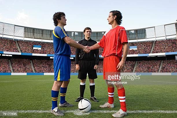 Opposite football player shaking hands