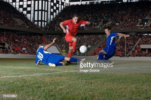 Opposite players tackling footballer : Stock Photo