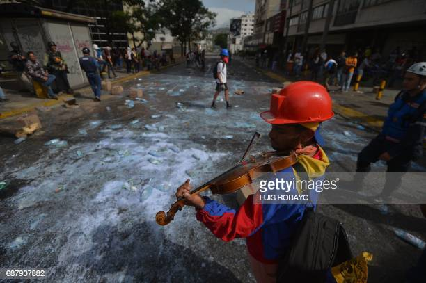 TOPSHOT Opposition activist Wuilly Arteaga plays the violin during a protest against President Nicolas Maduro in Caracas on May 24 2017 Venezuela's...