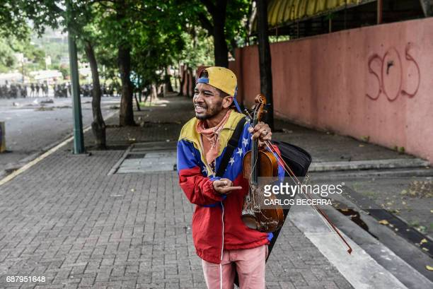 Opposition activist Wuilly Arteaga shows his broken violin during a protest in Caracas on May 24 2017 Venezuela's President Nicolas Maduro formally...