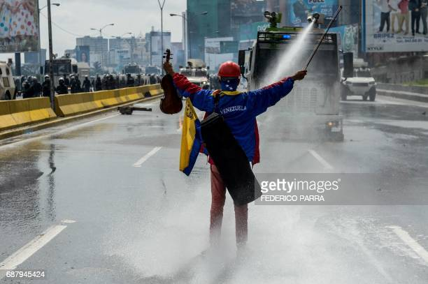 TOPSHOT Opposition activist Wuilly Arteaga stands with a violin in front of an armoured vehicle of the riot police during a protest against President...
