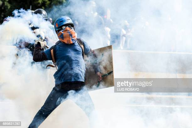 TOPSHOT Opposition activists and riot police clash during a demonstration against President Nicolas Maduro's government in Caracas on May 29 2017...