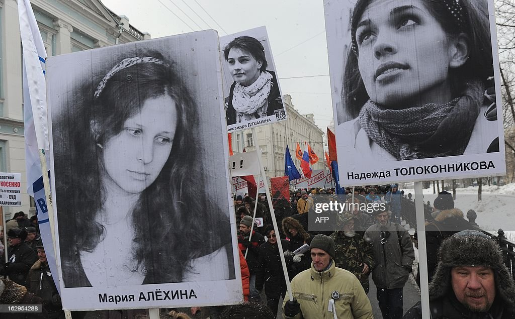 Opposition activists attend in Moscow on March 2, 2013 an anti-government rally to defend political and social rights of Moscuvites and to protest against city authorities' policy. Demonstrators also demanded to release political prisoners holding the portraits of jailed members of the female punk band 'Pussy Riot' Maria Alyokhina (L) and Nadezhda Tolokonnikova (R).