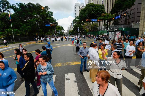 Opposition activists block an avenue in Caracas as they demonstrate against the government of President Nicolas Maduro on June 26 2017 A political...