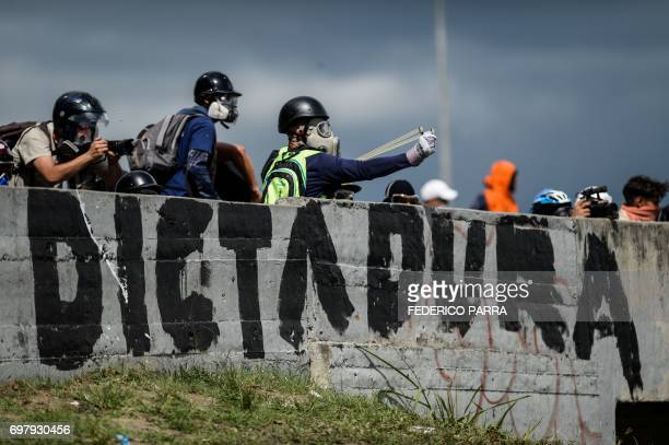 TOPSHOT Opposition activists clash with riot police during a demonstration against the government of President Nicolas Maduro along the Francisco...