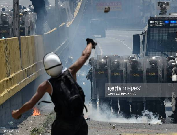 TOPSHOT Opposition activists clash with riot police during a protest against President Nicolas Maduro in Caracas on May 10 2017 Venezuelan protesters...