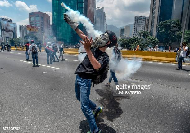 TOPSHOT Opposition activists clash with riot police during a protest march in Caracas on April 26 2017 Protesters in Venezuela plan a highrisk march...