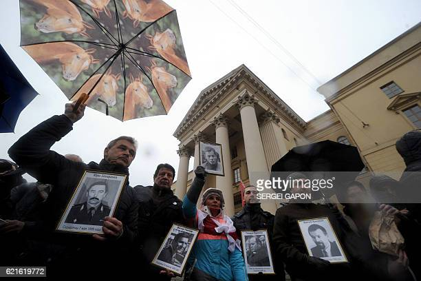 Opposition activists hold portraits of missing people during a rally in front of the KGB state security committee headquarters in Minsk on November 7...