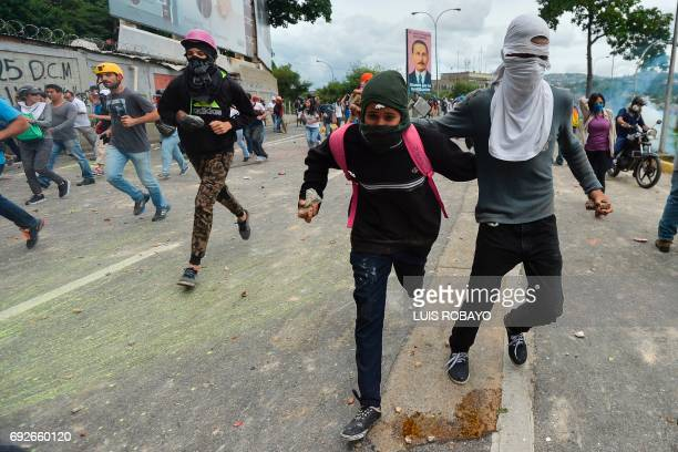 Opposition activists run during clashes with the riot police during a demonstration against President Nicolas Maduro's government in Caracas on June...