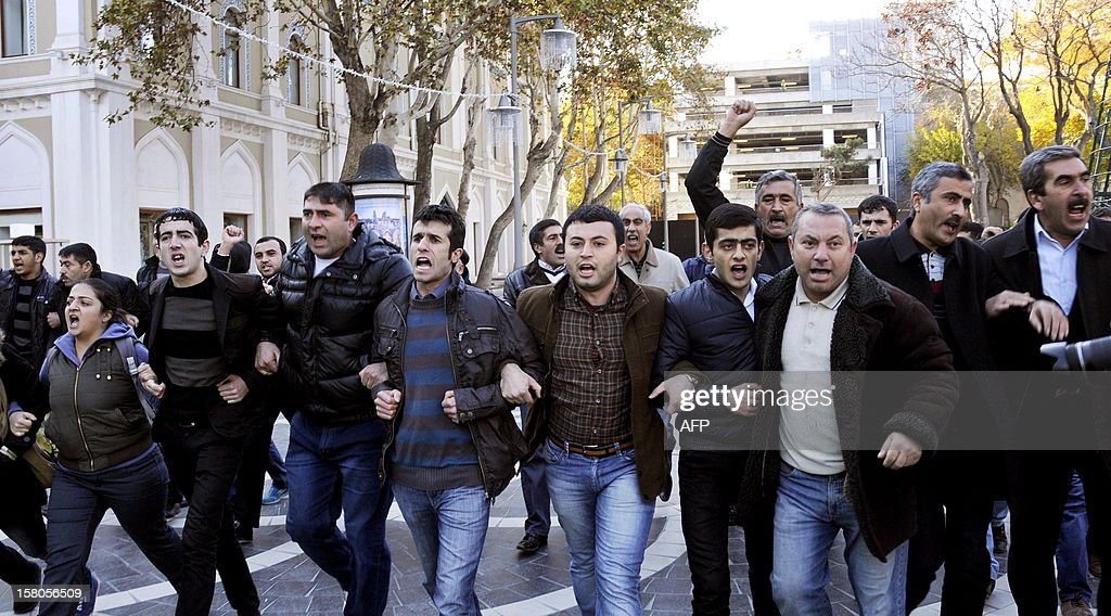 Opposition activists shout as they try to hold an unauthorized rally to demand the resignation of President Ilham Aliyev at the Fountains Square in in central Baku, the capital of Azerbaijan, on December 10, 2012. Police disperced today the unauthorised pro-democracy protest.