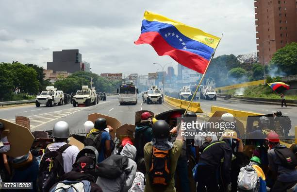TOPSHOT Opposition activists wave a Venezuelan national flag during clashes with riot police within a protest against Venezuelan President Nicolas...