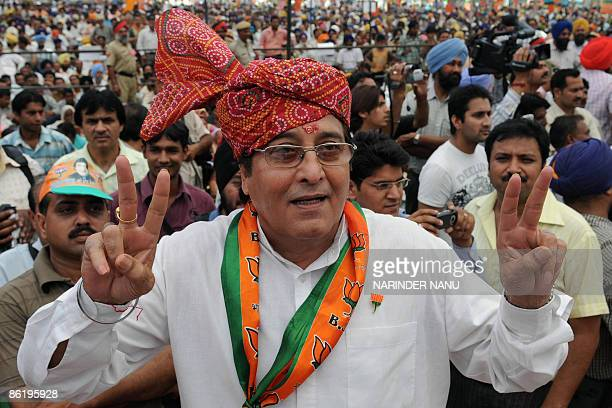 Opposition Bharatiya Janata Party candidate for Gurdaspur and Indian film actor Vinod Khanna makes a victory sign during an election campaign rally...