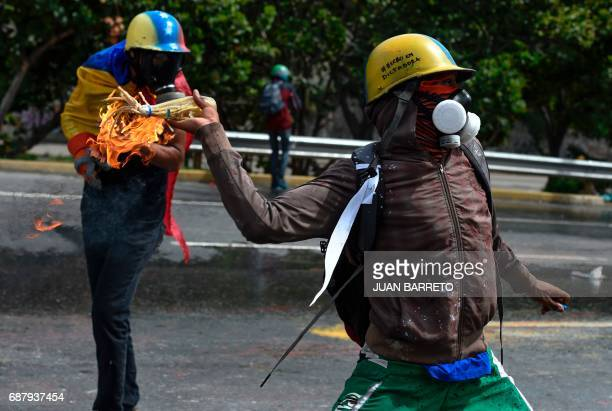 TOPSHOT Opposition demonstrators clash with riot police in Caracas on May 24 2017 Venezuela's President Nicolas Maduro formally launched moves to...
