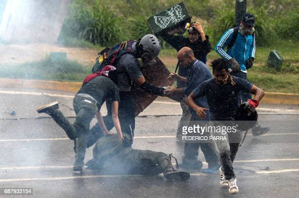 TOPSHOT Opposition demonstrators kick a riot policeman during clashes in Caracas on May 24 2017 Venezuela's President Nicolas Maduro formally...