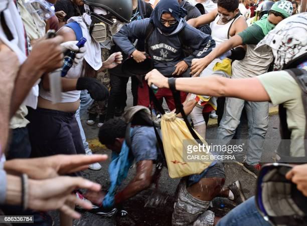 TOPSHOT Opposition demonstrators pour petrol over an alleged thief during a protest against the government of President Nicolas Maduro in Caracas on...
