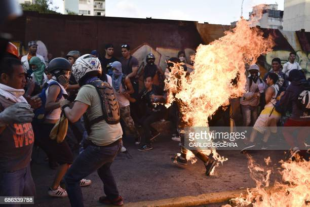 TOPSHOT Opposition demonstrators set an alleged thief on fire during a protest against the government of President Nicolas Maduro in Caracas on May...