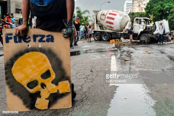 Opposition demonstrators stand next to a cement truck in clashes with riot police during a health care personnel march in Caracas on May 22 2017...