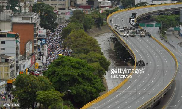 TOPSHOT Opposition demonstrators take part in a protest against President Nicolas Maduro in Caracas on May 24 2017 Venezuela's President Nicolas...