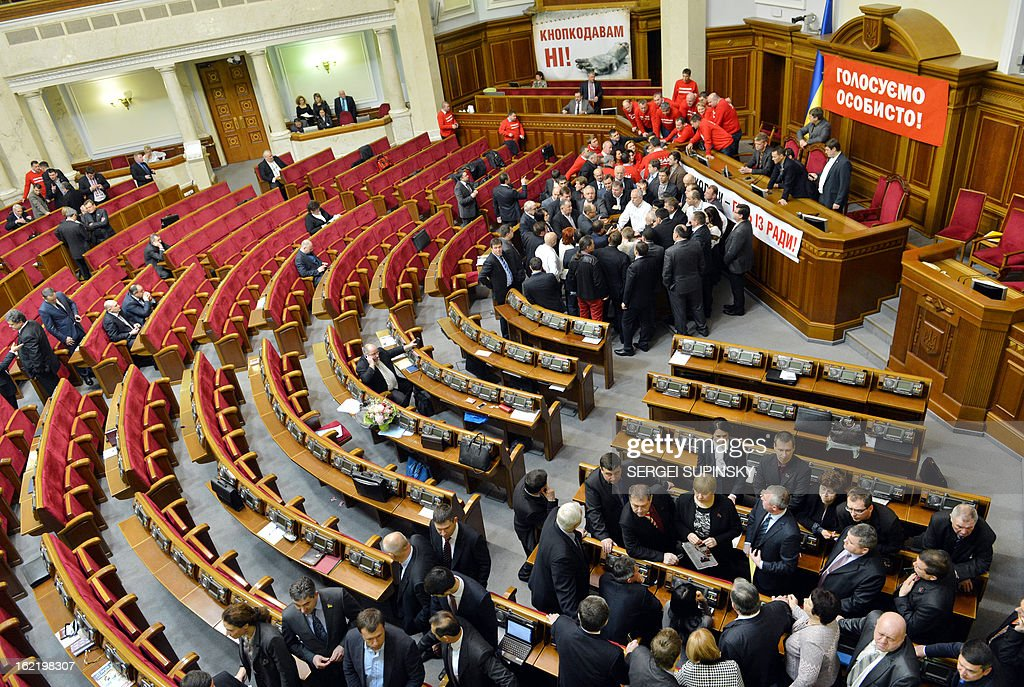 Opposition deputies wearing tee-shirts reading 'Vote personally' block the Ukrainian parliamentary in Kiev on February 20, 2013, as they try to prevent the opening of the session. The dispute in Ukraine's one-chamber parliament, known as the Verkhovna Rada, centres on opposition demands for each deputy to vote individually. Voting in the Ukrainian legislature is done electronically and lawmakers can delegate the right to vote to their colleagues.