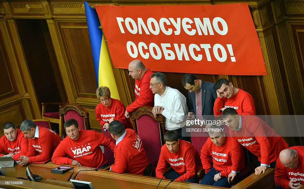 Opposition deputies wearing t-shirts reading 'Vote personally' block the Ukrainian parliamentary tribune, in Kiev on February 19, 2013, to prevent the opening of the session. The dispute in Ukraine's one-chamber parliament, known as the Verkhovna Rada, centres on opposition demands for each deputy to vote individually. Voting in the Ukrainian legislature is done electronically and lawmakers can delegate the right to vote to their colleagues. AFP PHOTO/ SERGEI SUPINSKY