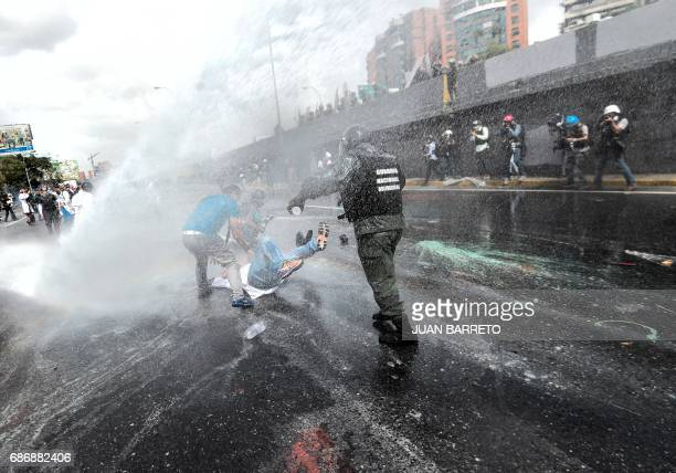 Opposition doctors and other health care personnel clash with riot police during a protest in Caracas on May 22 2017 Doctors rallied in Venezuela on...